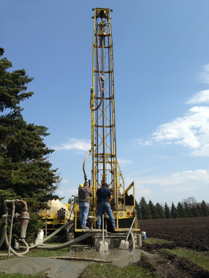 Schaefer Well Drilling employees drilling for water on a farm